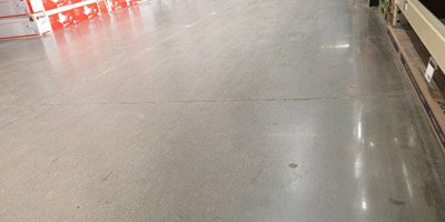 Polished concrete coating shows foot traffic patterns in the middle of this box store's aisle shows where the semi-topical sealer has worn off the concrete in a short time.