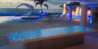 Fiber optic countertop on the beach with palm trees swaying in the wind.