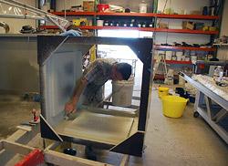 GFRC especialista em concreto aplica uma camada de névoa de GFRC a um molde de base de mesa.