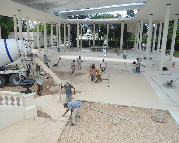 Concrete construction workers manufacturing a white cement covered area in Mexico Museum.