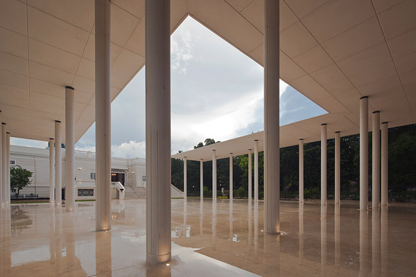 White cement U shaped building is a piece of art with its floating white cement roof panels atop slim white poles at a Mexican Mansion.