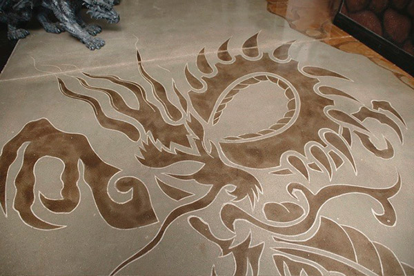 The image of a dragon on concrete was created with the help of a tattoo artist in Las Vegas who penciled in the lines for the concrete artist to cut and then stain with acid stain.