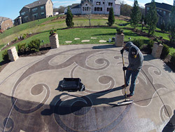 Sweeping a acid stained concrete patio that has been saw cut and acid stained.