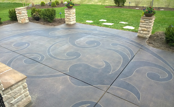 Stained and sealed concrete backyard patio after a saw cut design was placed in the concrete