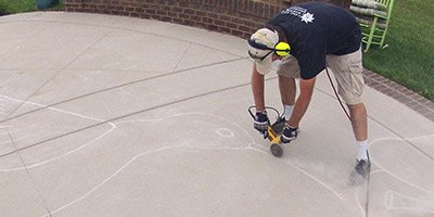 Concrete contractor using edge grinder with diamond blade to saw cut detail in a concrete slab.