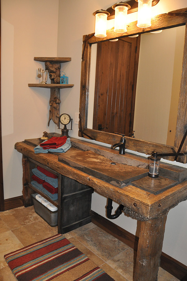 Bathroom vanity with a concrete sink and a slab of wood that is actually concrete as the countertop.