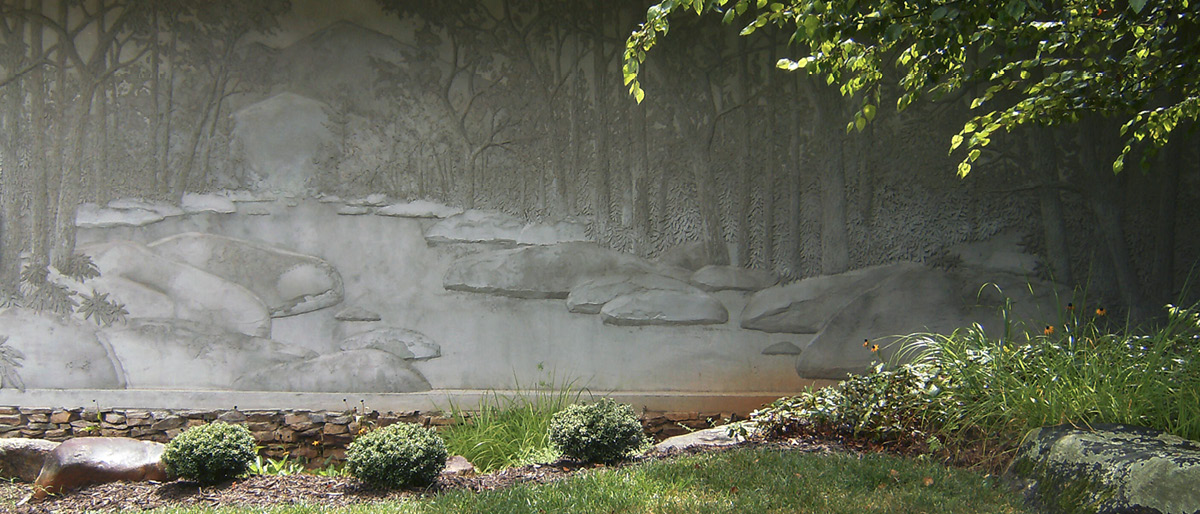 embedded concrete wall with trees and lake