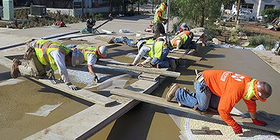 multiple construction workers using planks to keep them off the concrete