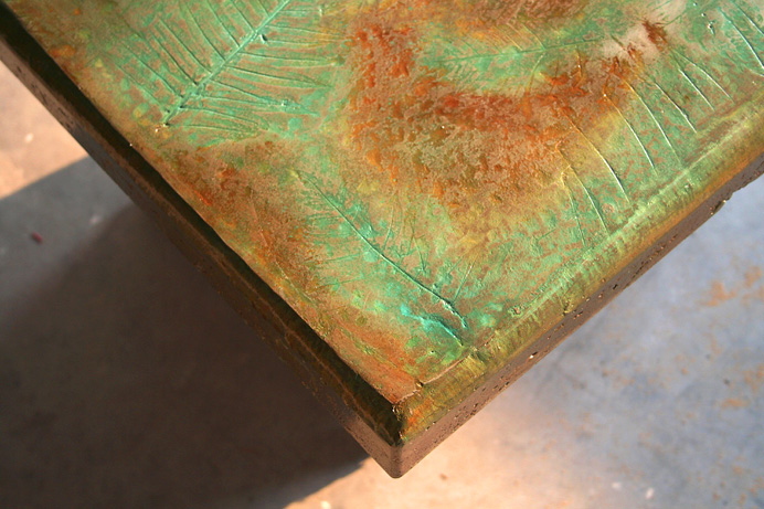 green and brown stained table with leaf imprints