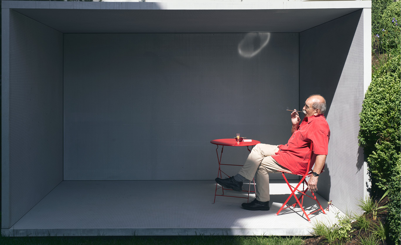 man sitting in a red chair smoking a cigar
