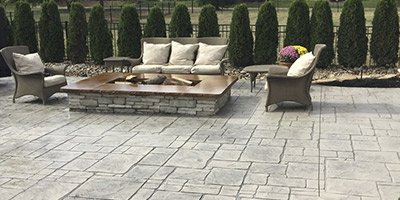 Stamped concrete patio with a square fire pit.