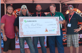 Dion Battles Vertical Concrete Creations, Nampa, Idaho wins the Brawl in the Fall at the Concrete Decor Show in San Diego is seen here with a huge check with SureCrete.
