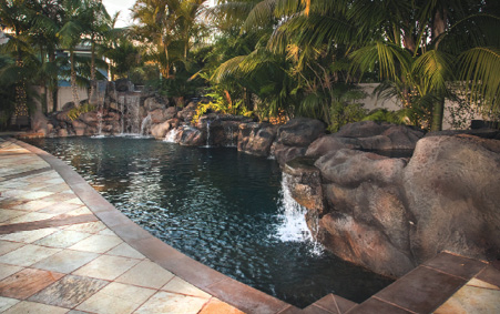 outdoor pool with concrete rock formations and stained floor