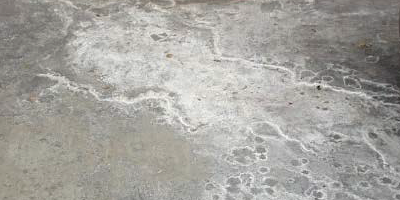 Efflorescence on a concrete garage floor needs moisture remediation help.