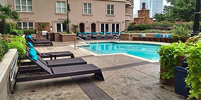 Serene setting at a upscale hotel where luxurious lounge chair sit atop a stamped concrete pool deck.