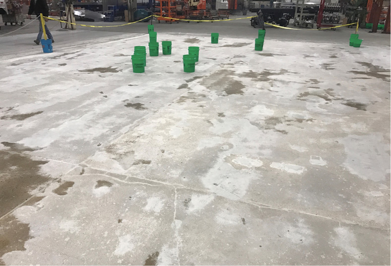 Metal screws can be seen as preparation got underway with diamond grinding of the damaged concrete floor to produce a relatively uniform concrete surface, followed by a considerable amount of patching the concrete defects and damage.
