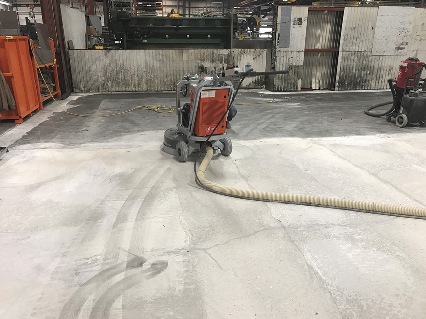 Removing excess sand from the broadcasting of silica sand into the still-wet polymer material on the concrete.