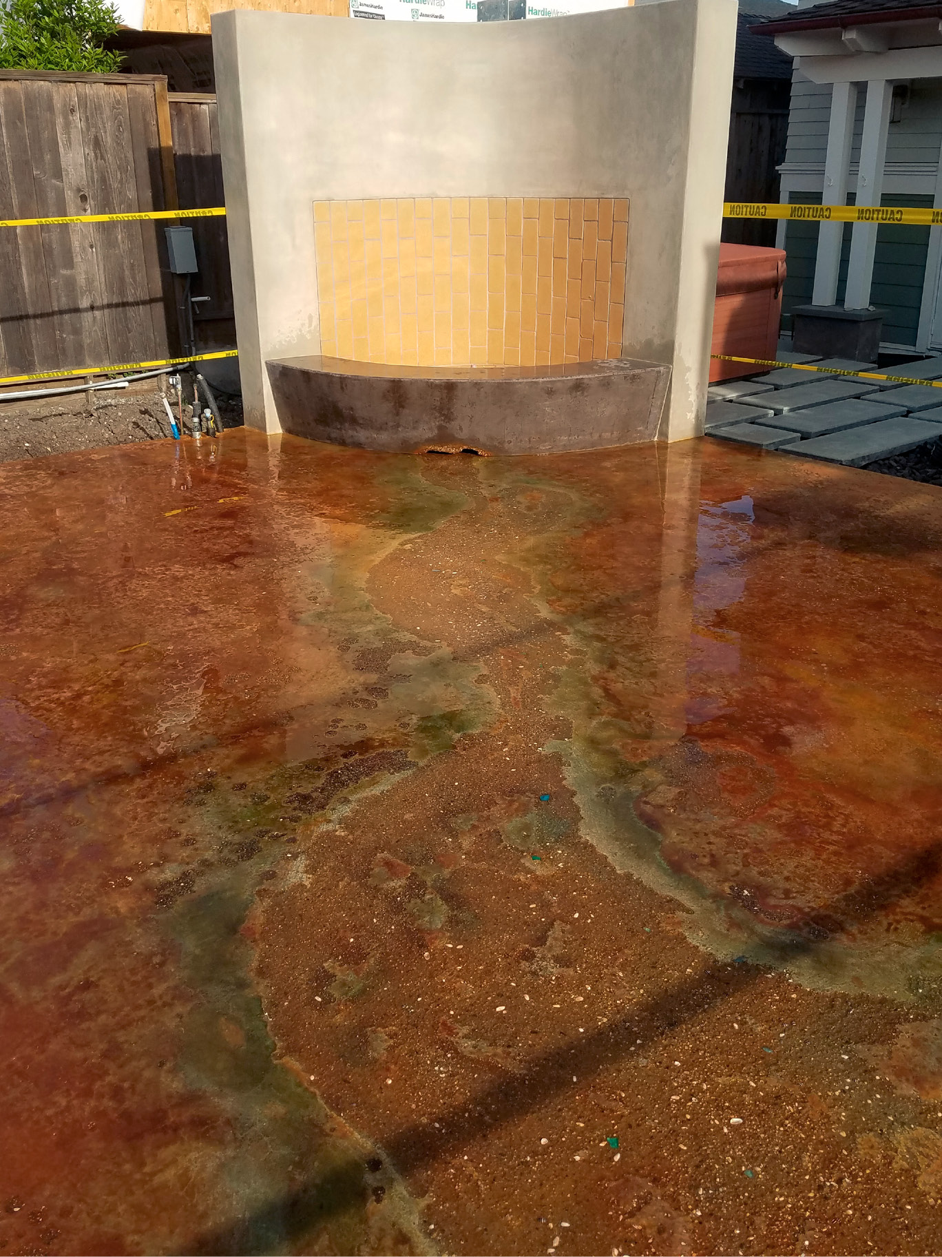 Concrete surface retarder applied to this surface exposes aggregates, seashells and beach glass to form a meandering river emerging from under a fireplace seat wall. Photo courtesy of Tom Ralston Concrete