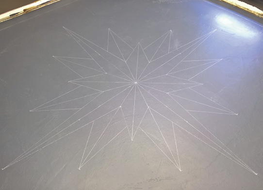 Chalk drawing of a compass rose on a floor.