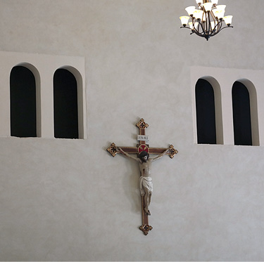 Crucifix hangs on a seminary wall below six arched openings coated with a polymer modified concrete coating made by Pure Texture.