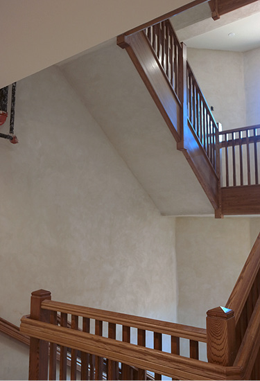 Four story stair well with wood hand rails in a seminary is coated off white with a product from Pure Texture.