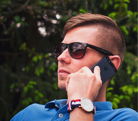Manscaped man with stylish sunglasses using a cell phone outdoors near a tree.