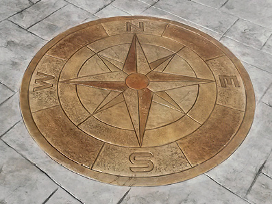 Stamped concrete compass pattern stained a darker color than the stamped concrete surround.