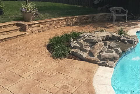 A stamped overlay surrounding an in ground pool with a faux rock feature water fall pouring into the pool.