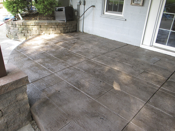Contractor Jim Boyce created this rustic wood-looking patio by stamping an overlay with Butterfield's Gilpin's Fall Bridge Plank pattern. The topping was colored with Butterfield's Burnished Taupe and antiqued with Storm Gray and Deep Charcoal.