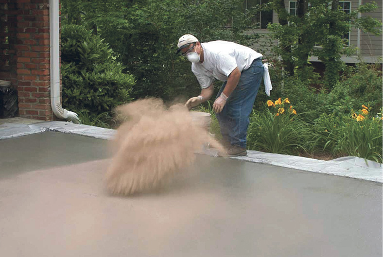 Concrete contractor wearing appropriated personal safety protection while throwing color hardener for concrete.