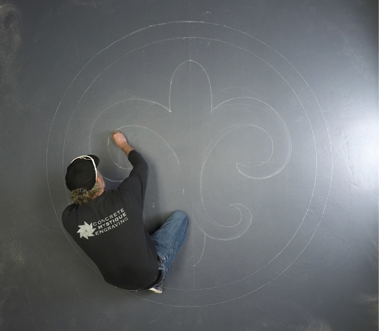 Finishing off the curves of a fleur-de-lis drawing on a concrete floor.