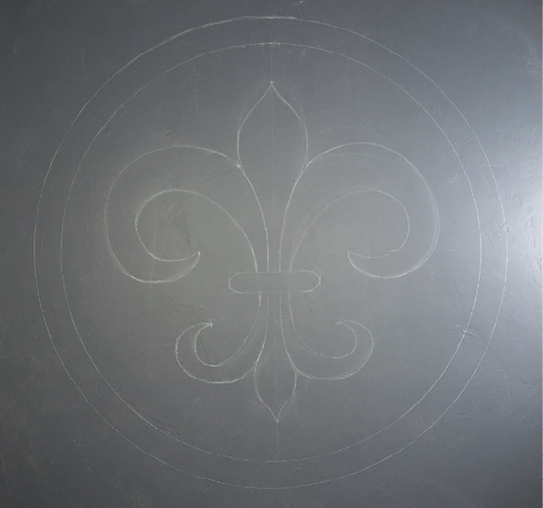 A finished chalk drawing of a fleur-de-lis on a concrete floor ready to be stained with water-based concrete stain.