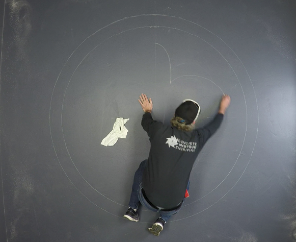 How to draw a circle on a concrete floor using a chalk box and string.
