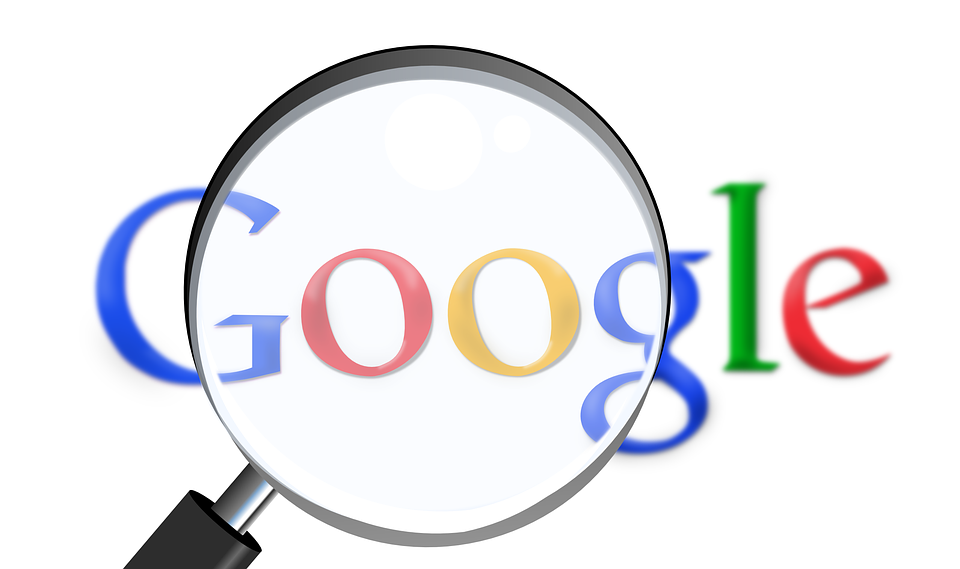Google logo with magnify glass held over it.