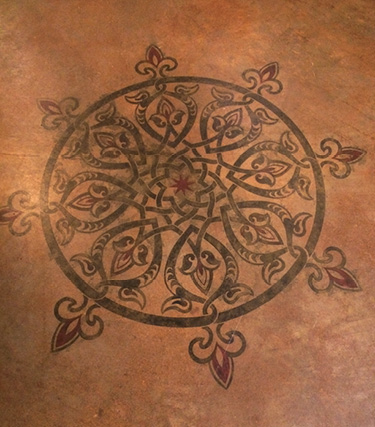 Stenciled medallion on a stained concrete floor.