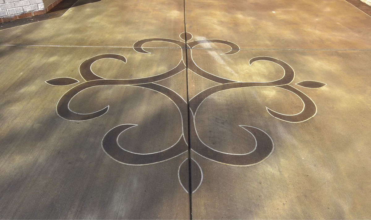Stained and saw cut concrete with a medallion stained a richer color.