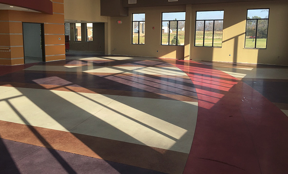 A large room with lots of windows showing off multiple colors in concrete on the floor.