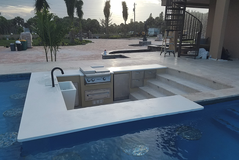 Cool sunk-in kitchen attached to a swimming pool where the concrete bar top hangs over the pool.