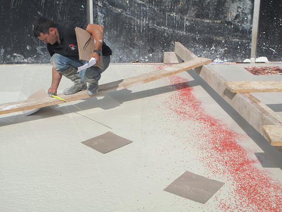 Concrete contractor placing stencil in pure white cement overlay spiked with red glass aggregate.