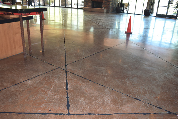 After the black polyurea joint filler had been applied the overfill was cut back and the floor is ready to be ground and polished.