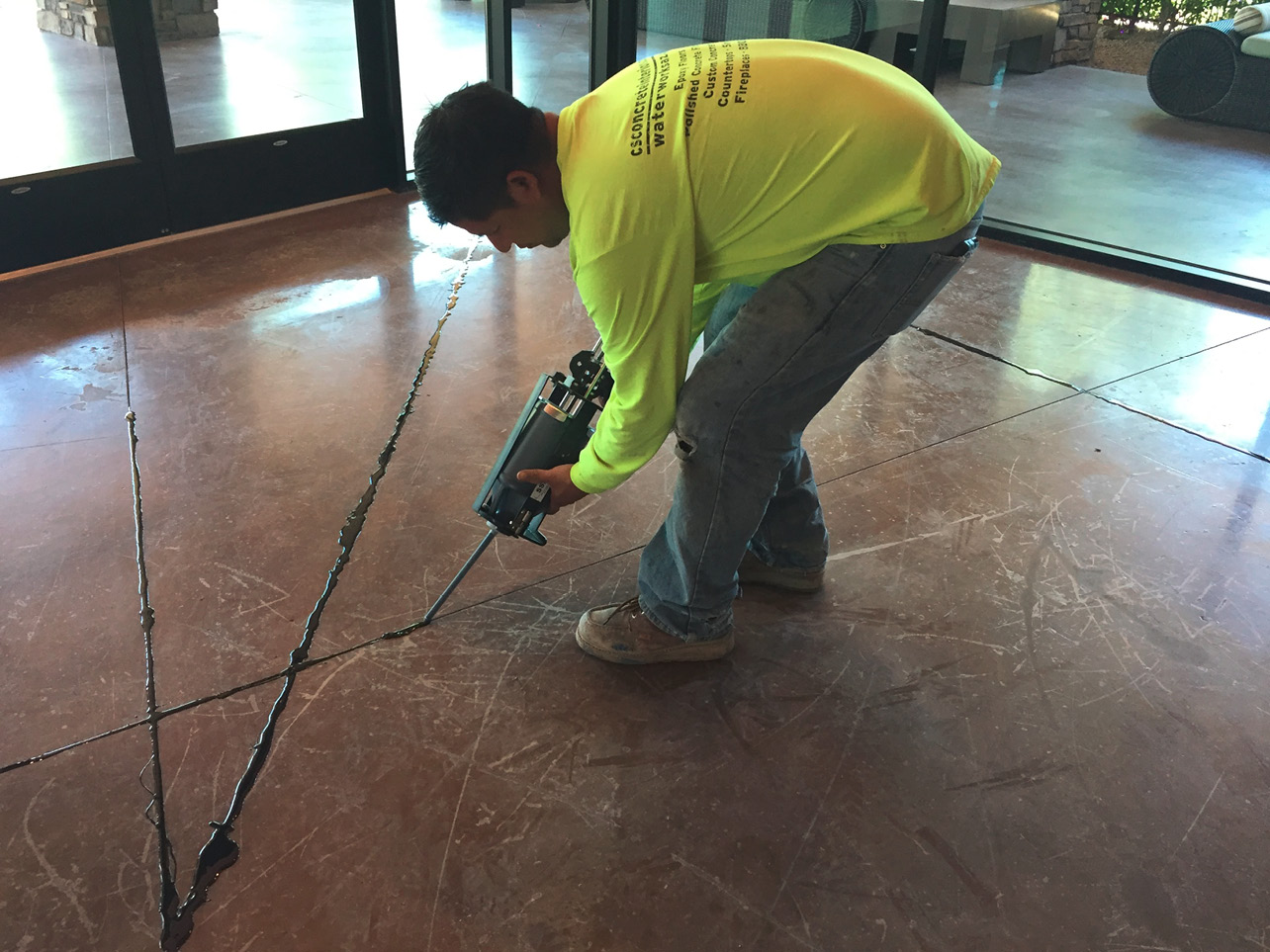 A crew member uses a cartridge of Solid Solution Products polyurea to fill joints on a polished concrete job. Photo courtesy of Concrete Interiors