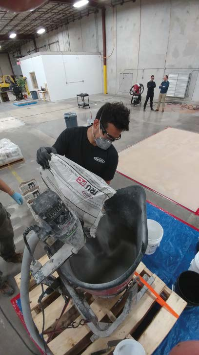 A crew member adds a self-leveling overlayment to a high-speed stand mixer.