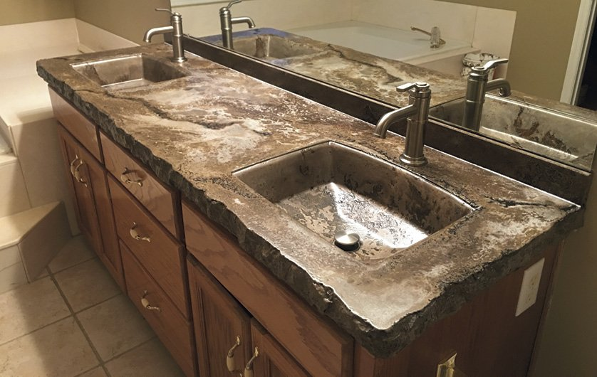 Brown multicolored concrete countertop in a bathroom with two integral sinks. Photos courtesy of Concrete In-Counters