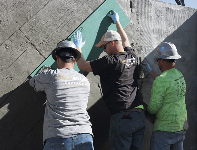 Three gentleman holding up a stamp to create would looking vertical concrete wall at Concrete Decor's Decorative Concrete Live at World of Concrete 2018.