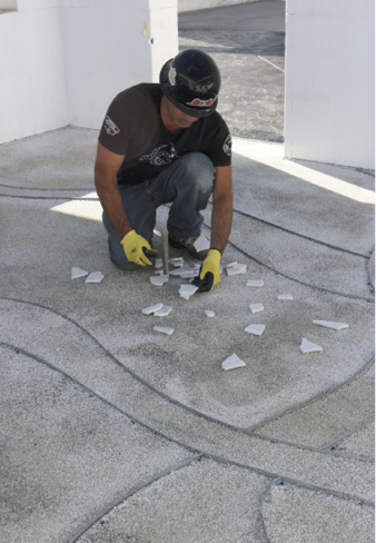Miguel Lopez places glass into the flooring at Concrete Decor's Decorative Concrete Live at World of Concrete 2018.