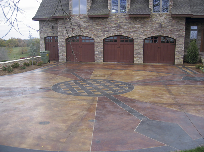 This driveway has three major color areas. The borders and interwoven designs are a warm black. Some of the triangle-shaped areas are a very warm reddish-brown, while the other areas are more of a tan.