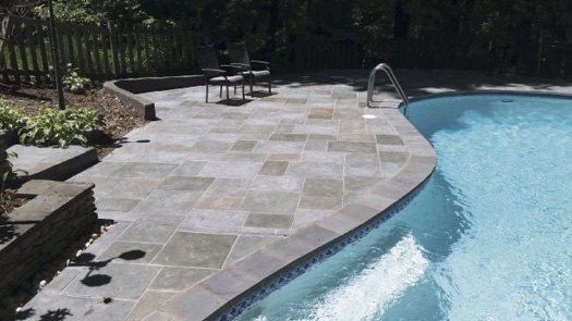 Tired of the high maintenance of their existing stone pavers, the clients opted for multicolored stamped concrete with grouting detail in an Old English Slate pattern and a zero-shine sealer.