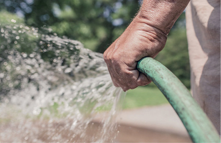 Spraying water from a green water hose on to a concrete surface.