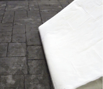 Removing Concrete Sealer with a blanket - When the blanket is dry and impregnated with old acrylic sealer, peel it up.