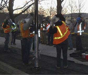 "A T.B. Penick crew performs its ""stretch-and-flex"" exercises to loosen up before starting the day's work at Myriad Gardens in Oklahoma City. Following this routine, they review safety procedures specific to the task at hand. Webcor also has a similar safety program in place."
